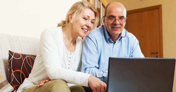 senior couple looking at laptop screen