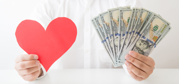 man holding cut-out paper heart and money