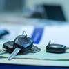 Car keys on top of auto insurance policy papers